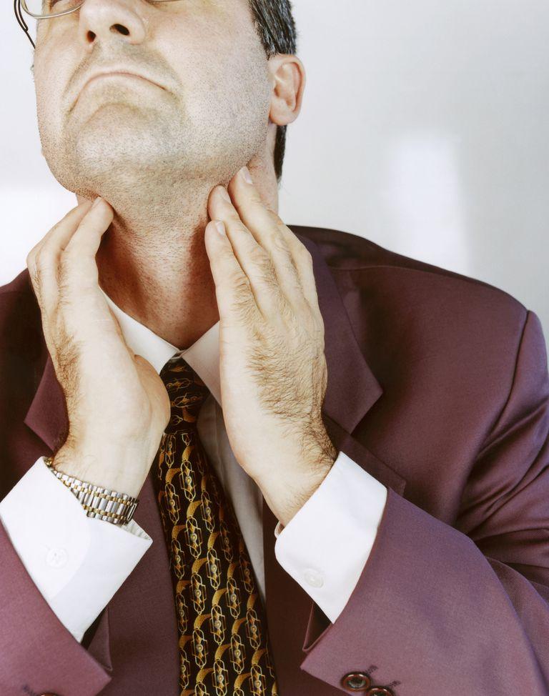 Man touching throat