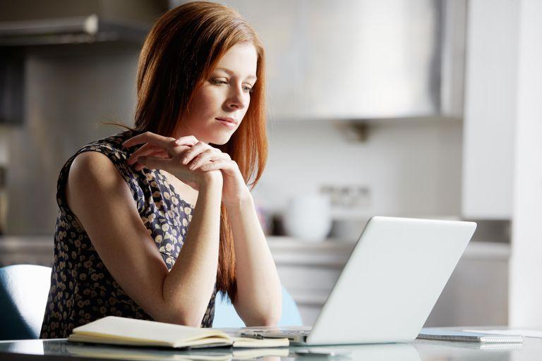 Woman looking at laptop screen, contemplating
