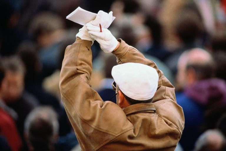 Bookmaker at a racecourse signaling in tick-tack with arms aloft