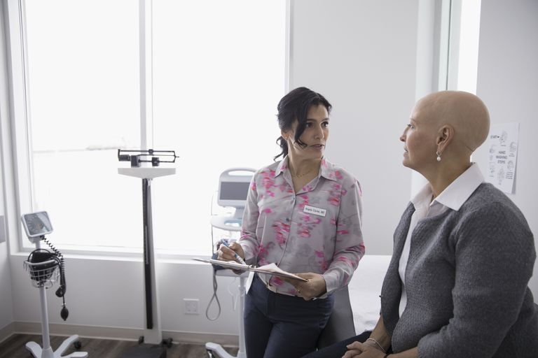 Female doctor and bald cancer patient talking in clinic examination room