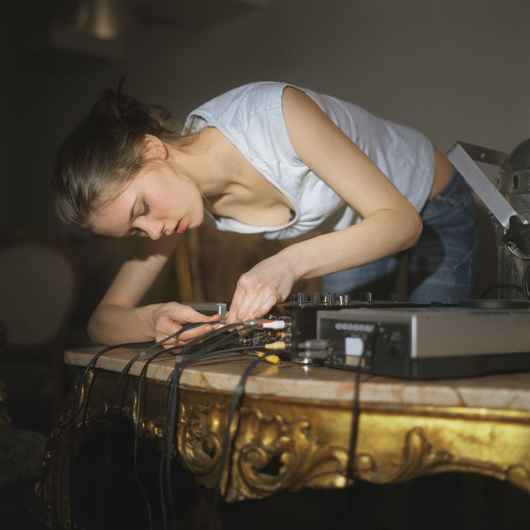 A young woman hooking cables to stereo equipment