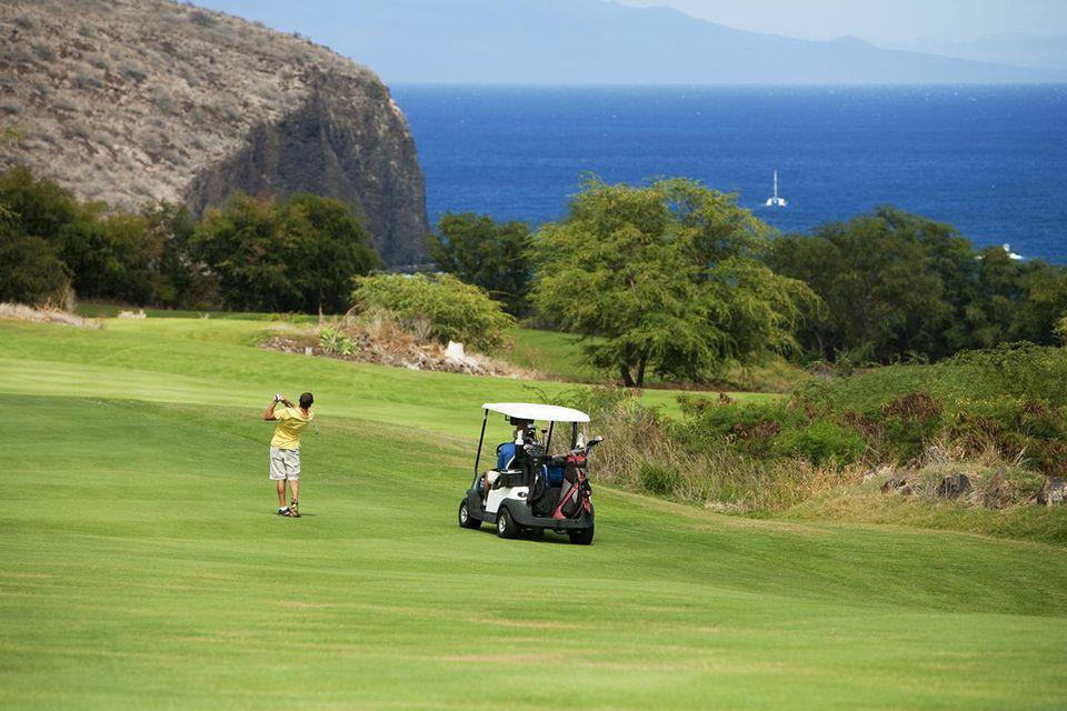 Hawaii, Lanai, Man playing golf at The Challenge at Manele Golf Course.