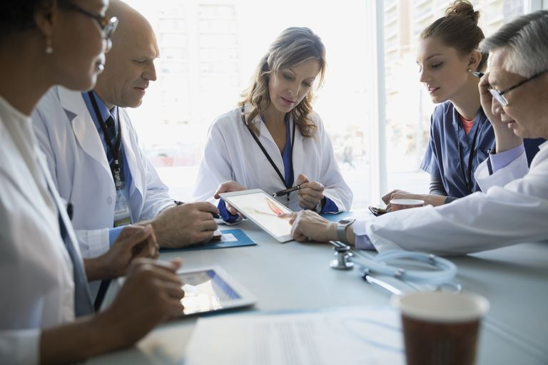 Female doctor meeting with other doctors and nurses