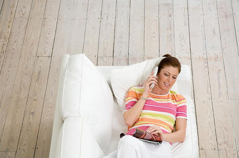 Woman on sofa with telephone and magazine