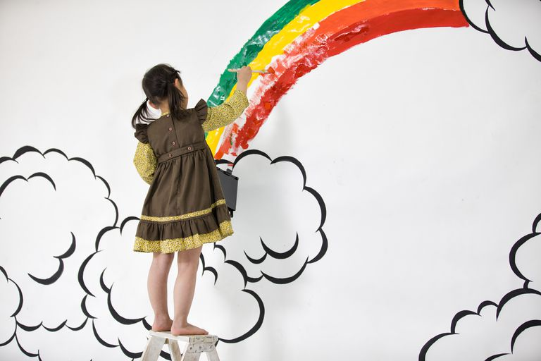Girl draw rainbow on the wall