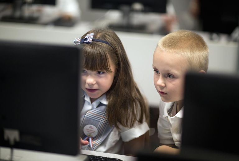 First grade school children learn on computers.