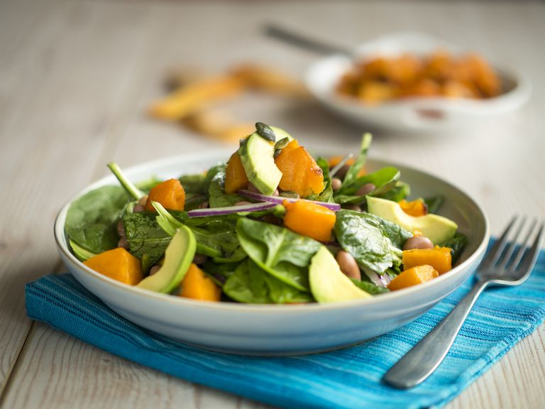 Spinach salad with avocado, onion, and roasted squash