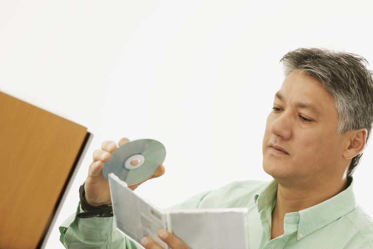 Close-up of a senior man holding a CD and a CD Case