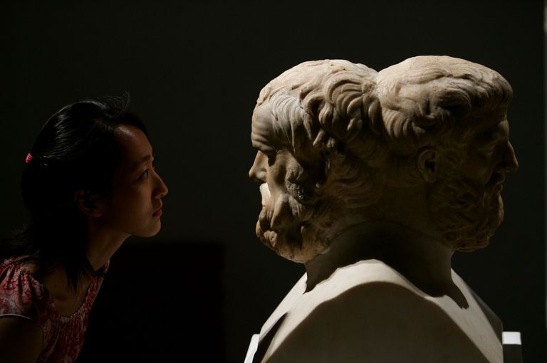 A visitor views a sculpture of Aristophanes and Sophocles during an exhibition of ancient Greek art from the Louvre Museum on August 11, 2007 in Beijing, China.