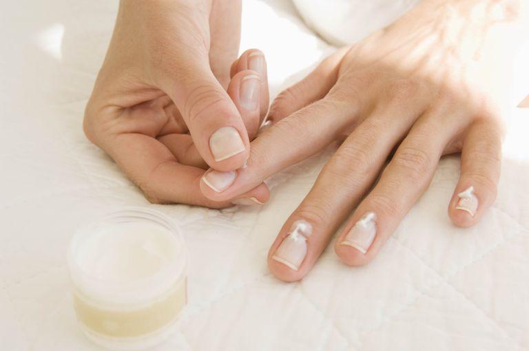 Woman applying cuticle cream