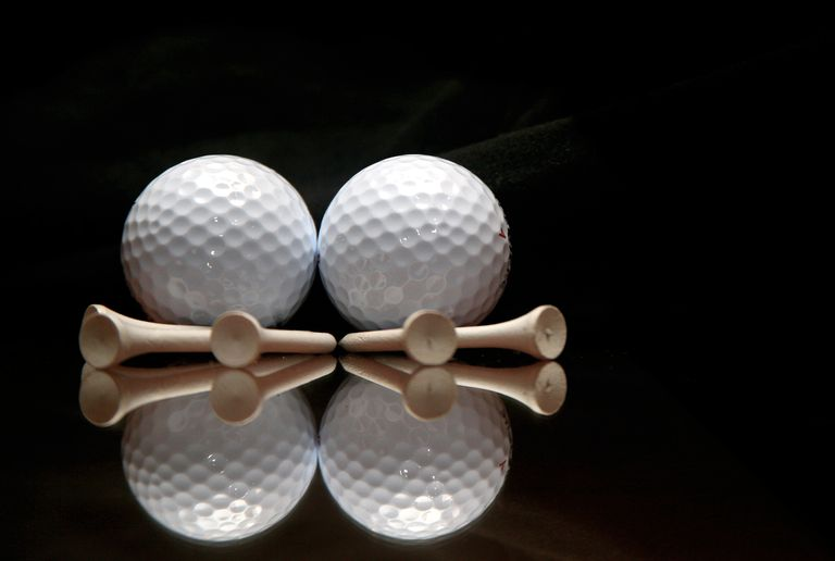 Dimples shows on two golf balls and their reflection