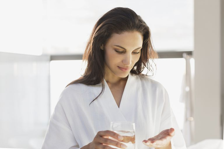 Woman wearing a bathrobe taking a pill