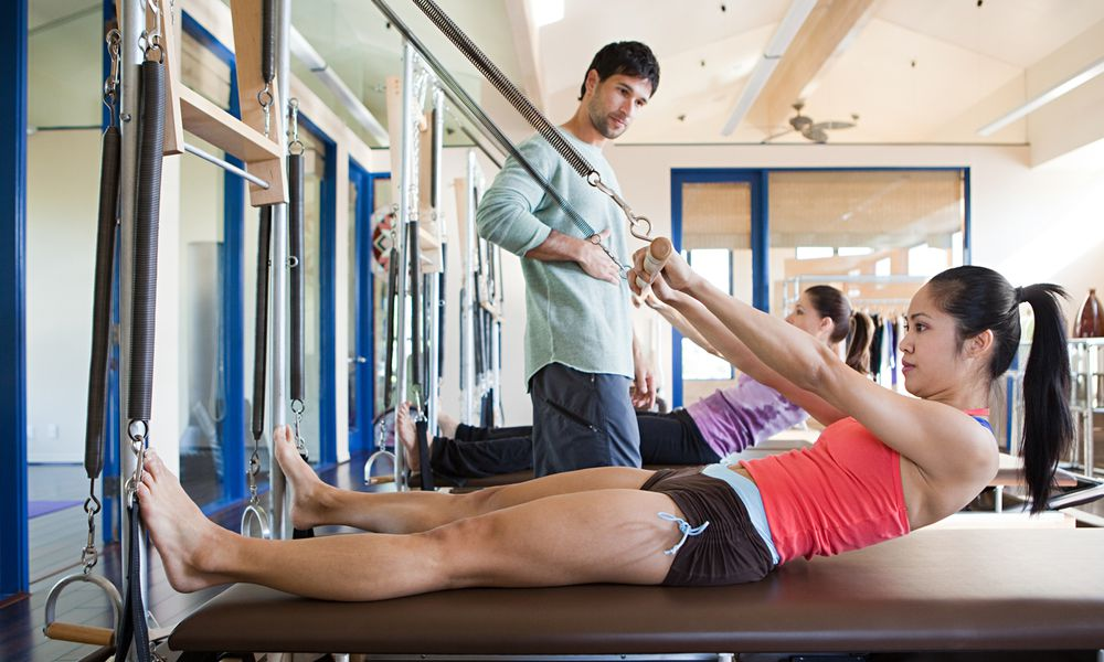 Two women work with a Pilates instructor.
