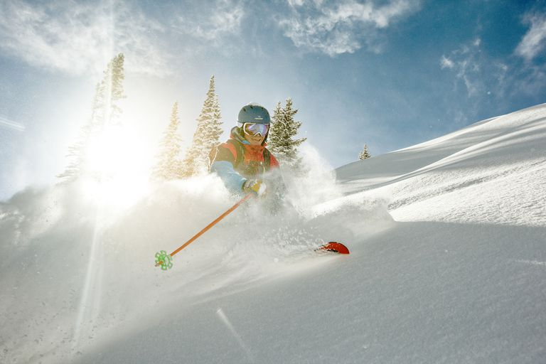 Skier taking a turn in deep powder on a sunny day