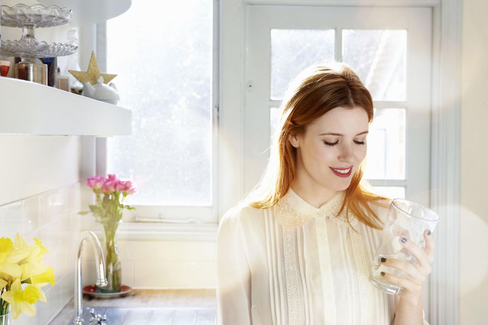 Woman smiling with glass of water in kitchen.