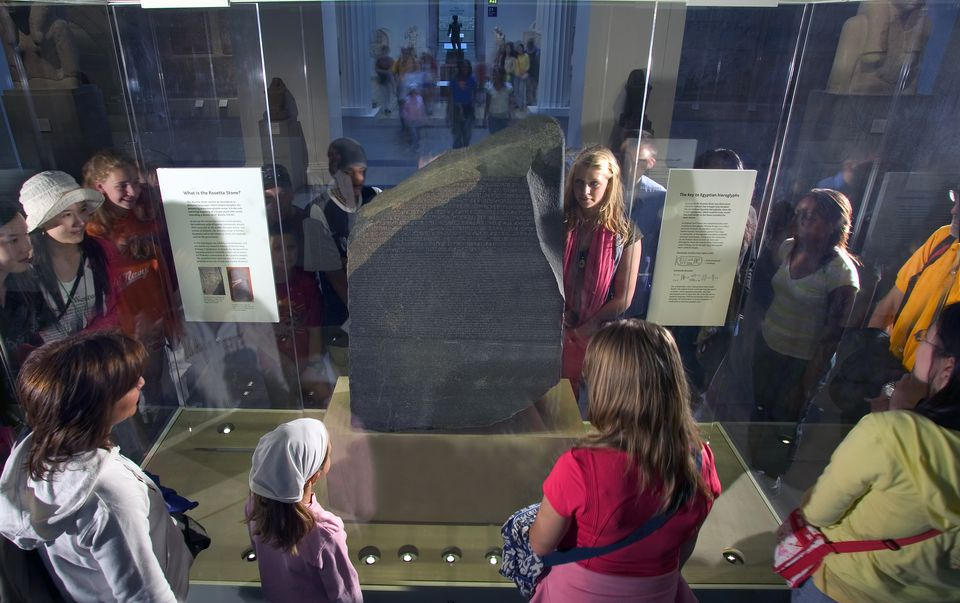 Visitors to the British Museum looking at the Rosetta Stone, a valuable key to the decipherment of hieroglyphs and our understanding of Ancient Egyptian culture, British Museum, London, London, England.