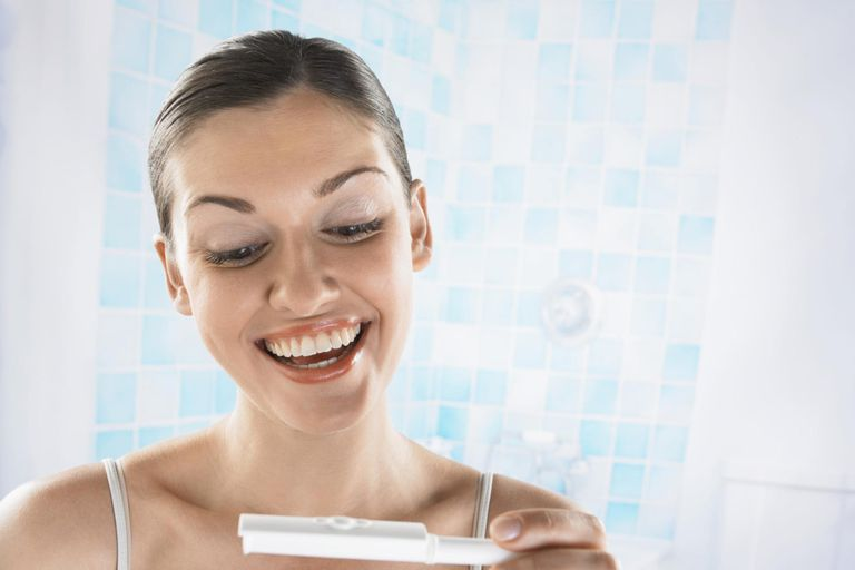 Happy Looking Woman Looking at a Pregnancy Test Stick.