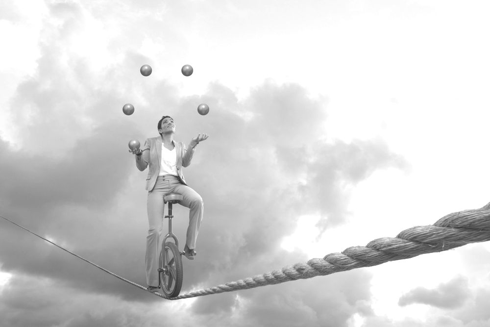 Man on a tightrope juggling - which requires a different type of balance than a balanced fund.