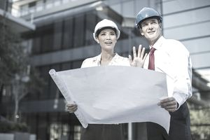 Architects reviewing blueprints outside urban building