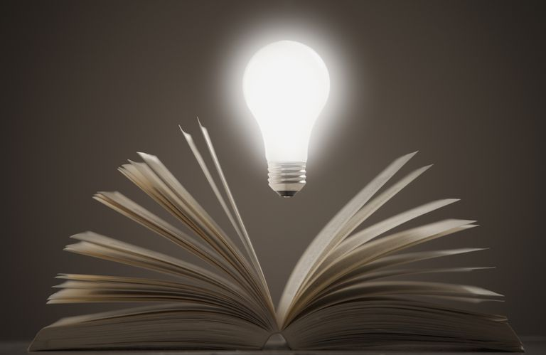 Light bulb floating above open book