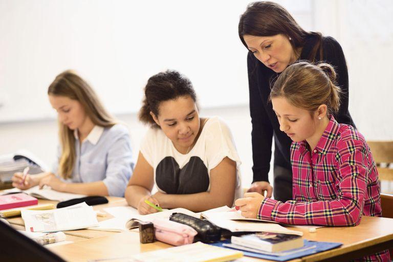 Mature female teacher teaching schoolgirls in classroom