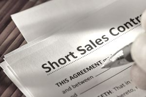 studio shot of hand signing short sale contract