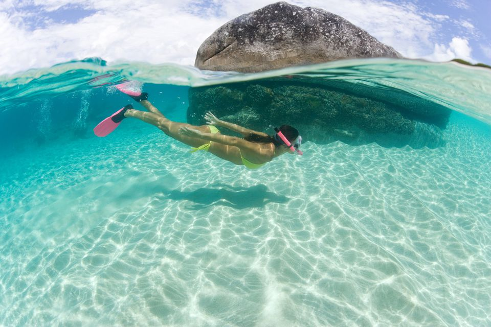 A woman snorkeling in clear waters