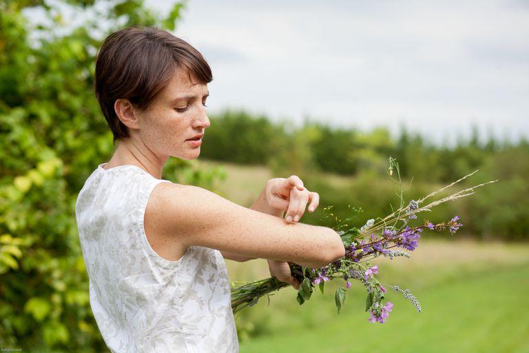 Woman examining arm outdoors