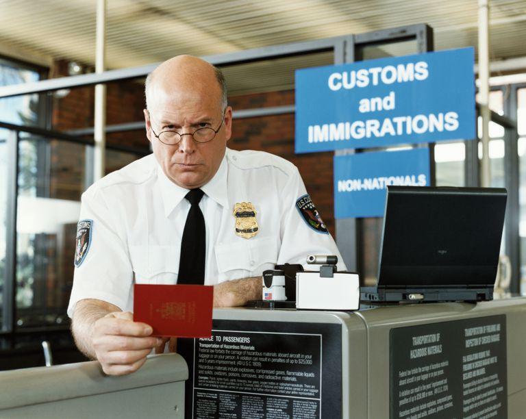Oficial migratorio verificando documento.