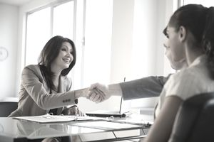 Businesswoman shaking hands with clients at desk