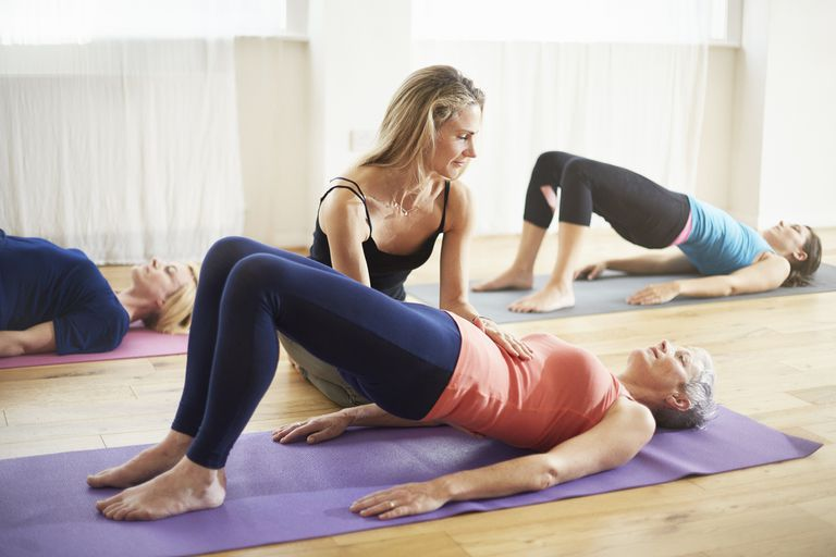 Teaching supporting student lying on back in pilates class