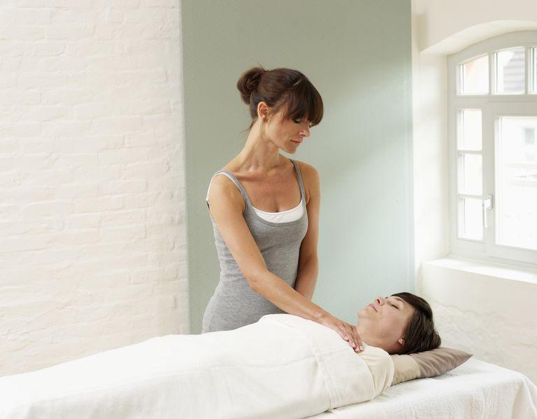 Woman receiving reiki treatment from masseur