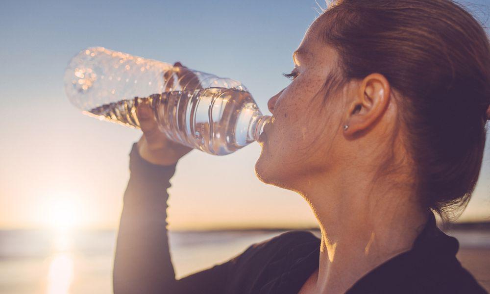 Woman drinking water seaside