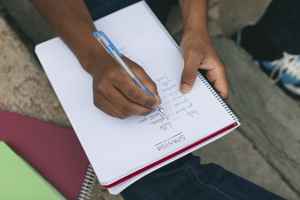 Writing Spanish Phrases in a Notebook