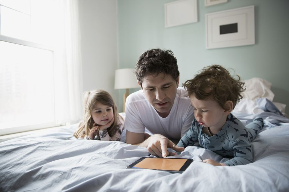 Father and children lying in bed with tablet