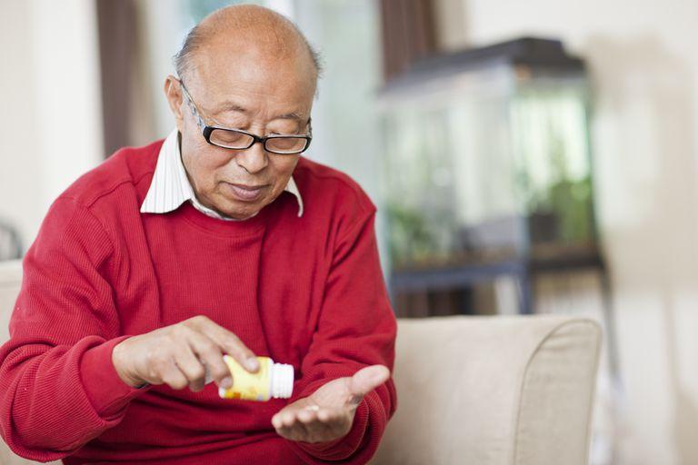 Man holding pill bottle and pill