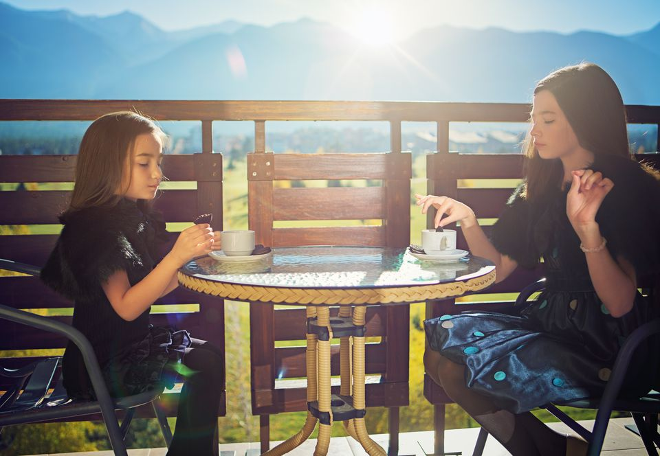Two girls having a tea party on a balcony