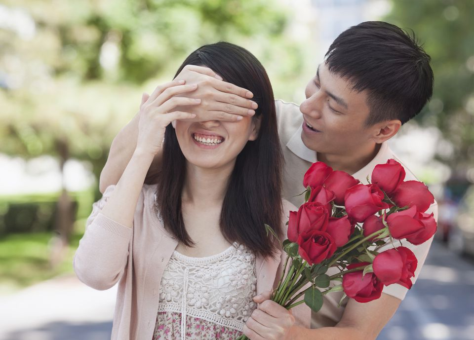 Asian man surprising girl friend with a bunch of red roses.