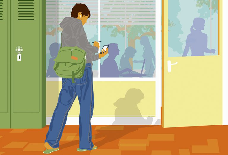 Student checking cell phone outside classroom