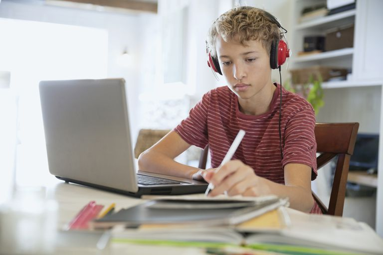 Young boy making notes on writing pad while using laptop and headphones at table