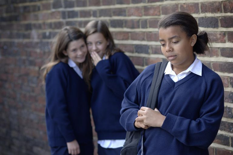 Two school girls (11-12) whispering and laughing at another girl (12-13), focus on front girl.