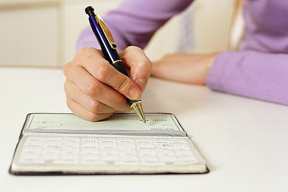 Woman writing in checkbook, close-up