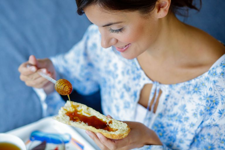 woman pooring honey on a piece of bread