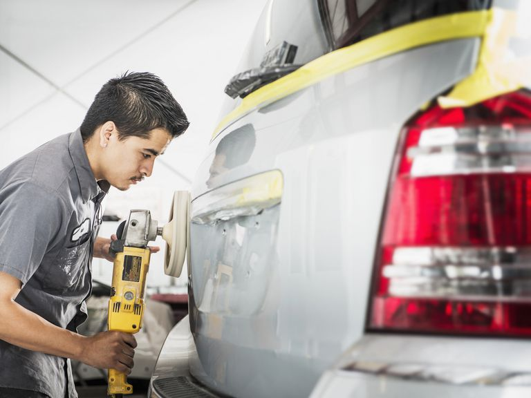 a paint technician buffing the paint on a recent auto body repair