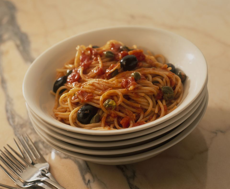 Spaghetti Puttanesca in bowl and a stack of bowls underneath