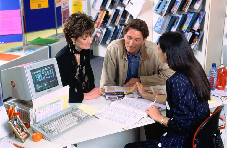 Young couple booking holiday, talking to female travel agent.