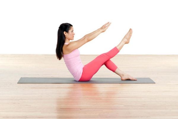 Woman practising Pilates mat exercise, side view