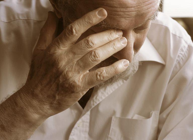 Senior man rubbing eye, close-up