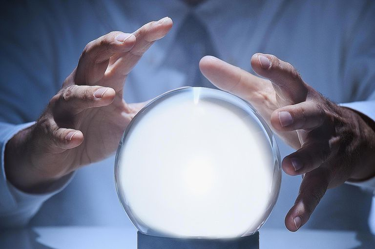 A man using a crystal ball to read the future symbolizes how a hypothesis in research predicts the outcome.