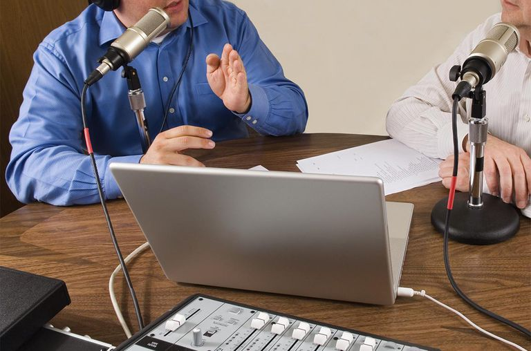 Two businessmen (no faces) sitting at a table recording a podcast
